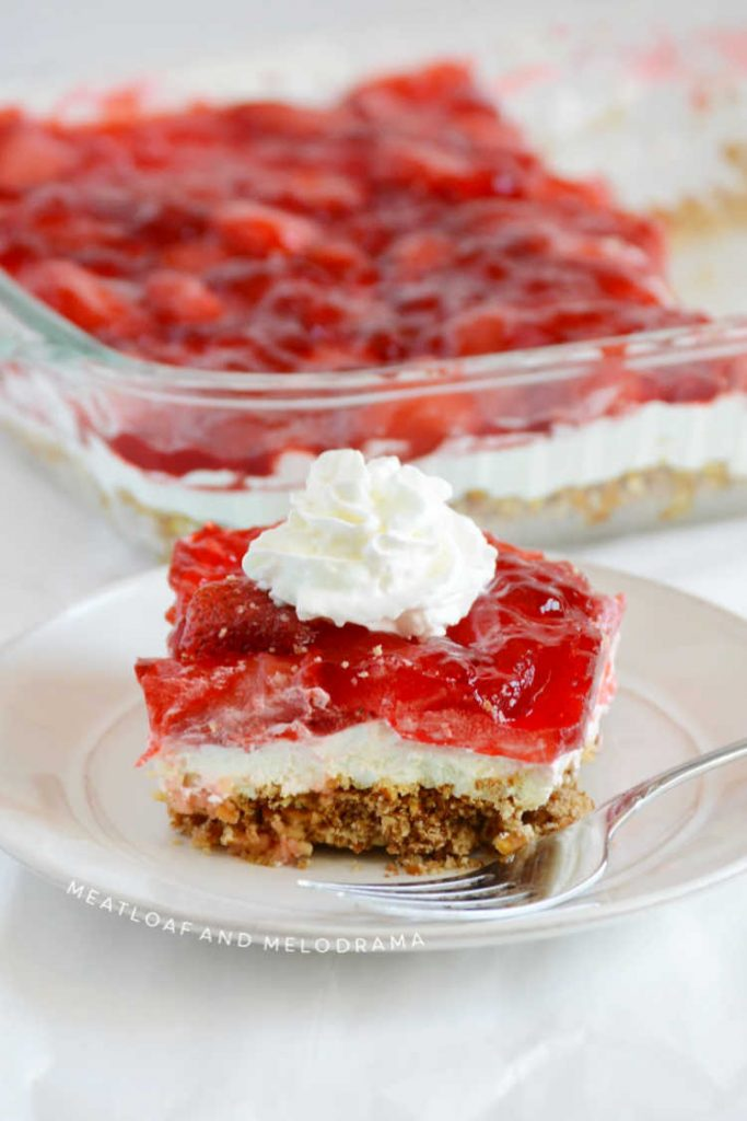 strawberry pretzel salad with whipped cream on a white plate