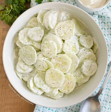 creamy cucumber salad in a white serving bowl