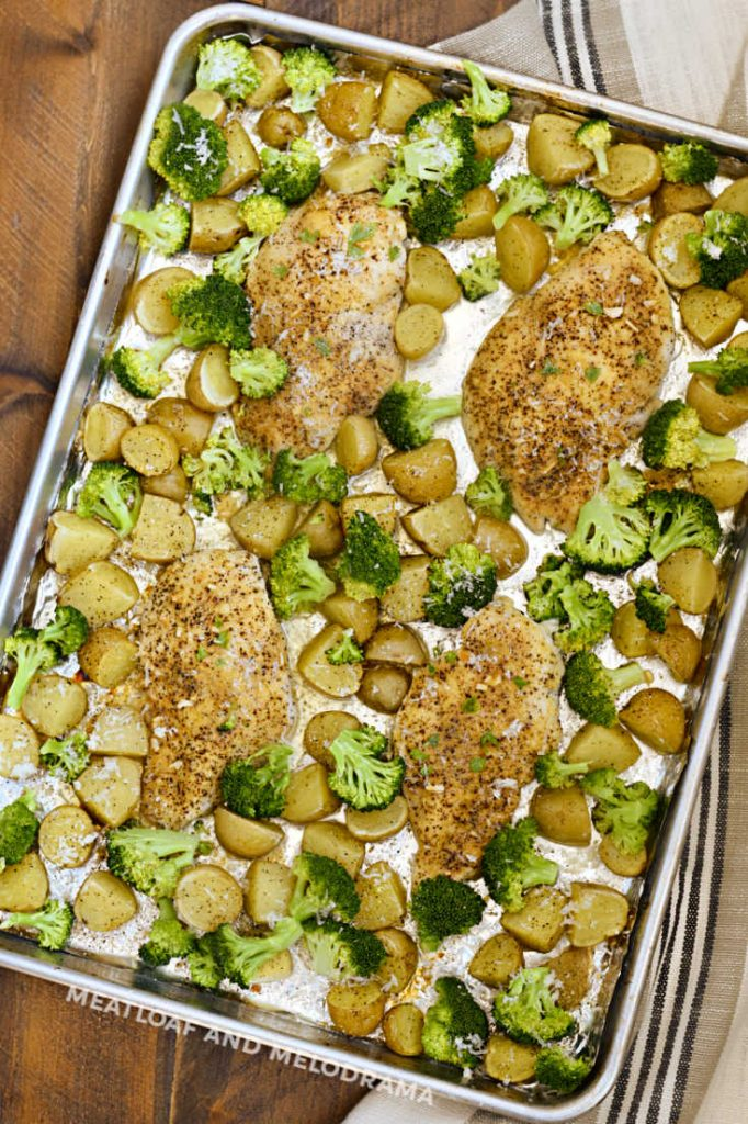 baked chicken and potatoes with broccoli on a sheet pan