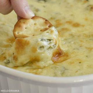 cheesy baked spinach artichoke dip on a round cracker