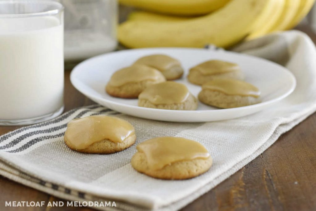 banana bread cookies with brown sugar frosting on a table with milk