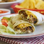 ground beef and black bean burritos with cheese, lettuce and tomatoes on plate