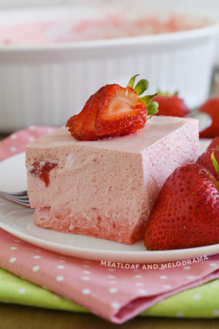 slice of strawberry jello salad with strawberries on a plate