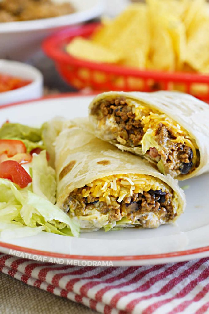 cut open ground beef burritos on a plate with lettuce and tomatoes
