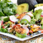 loaded southwest chicken salad with roasted corn and black beans over fresh greens