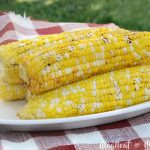 foil grilled corn on the cob on platter in backyard