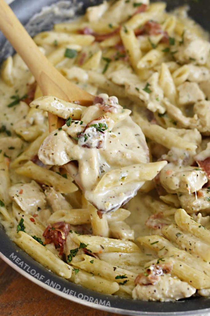ranch chicken pasta with bacon on a wooden spoon