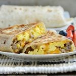 crispy sausage egg breakfast burritos on plate with fruit