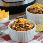 mom's best instant pot chili recipe in bowls with cheese topping