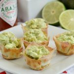avocado dip wonton cups on a platter with tabasco sauce