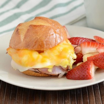 cheesy ham and egg breakfast sliders on plate with fruit