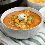 instant pot chicken enchilada soup in white bowl with sour cream, corn chips and cheese