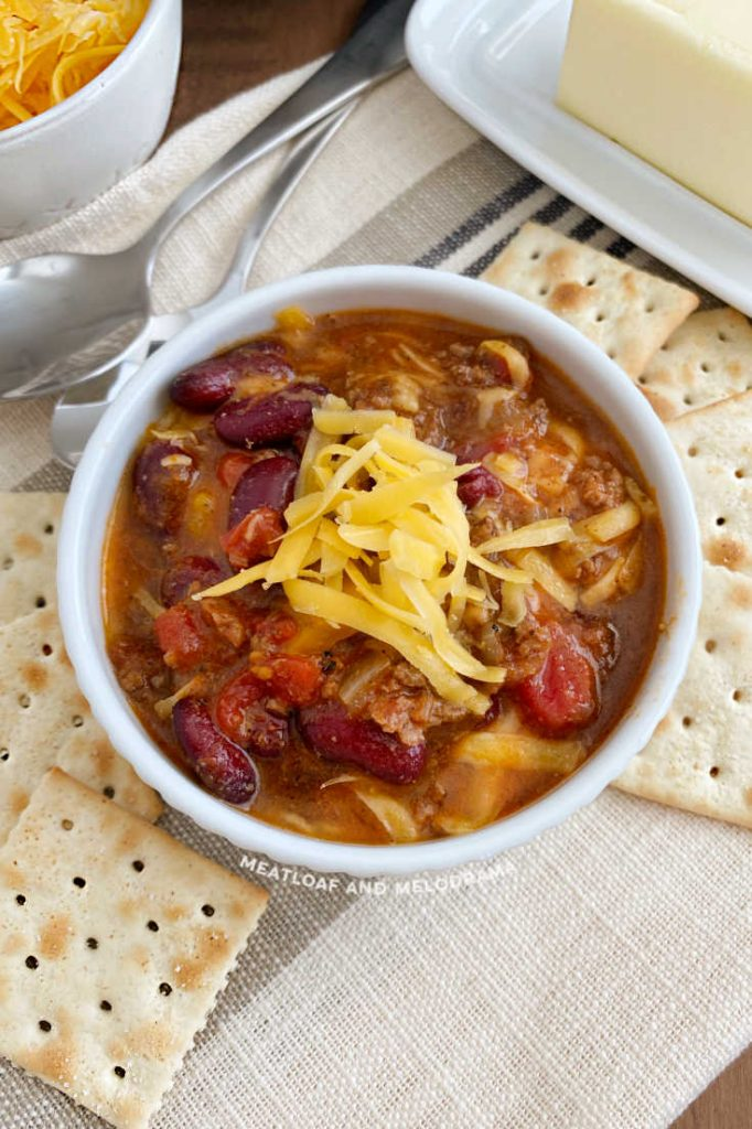 ground beef and bean chili in a white bowl with crackers