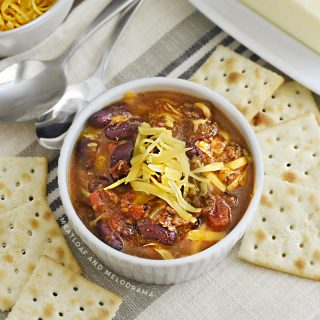 bowl of instant pot chili in white bowl with cheese and saltine crackers