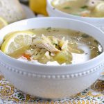 instant pot lemon chicken orzo soup in a bowl with lemon slices