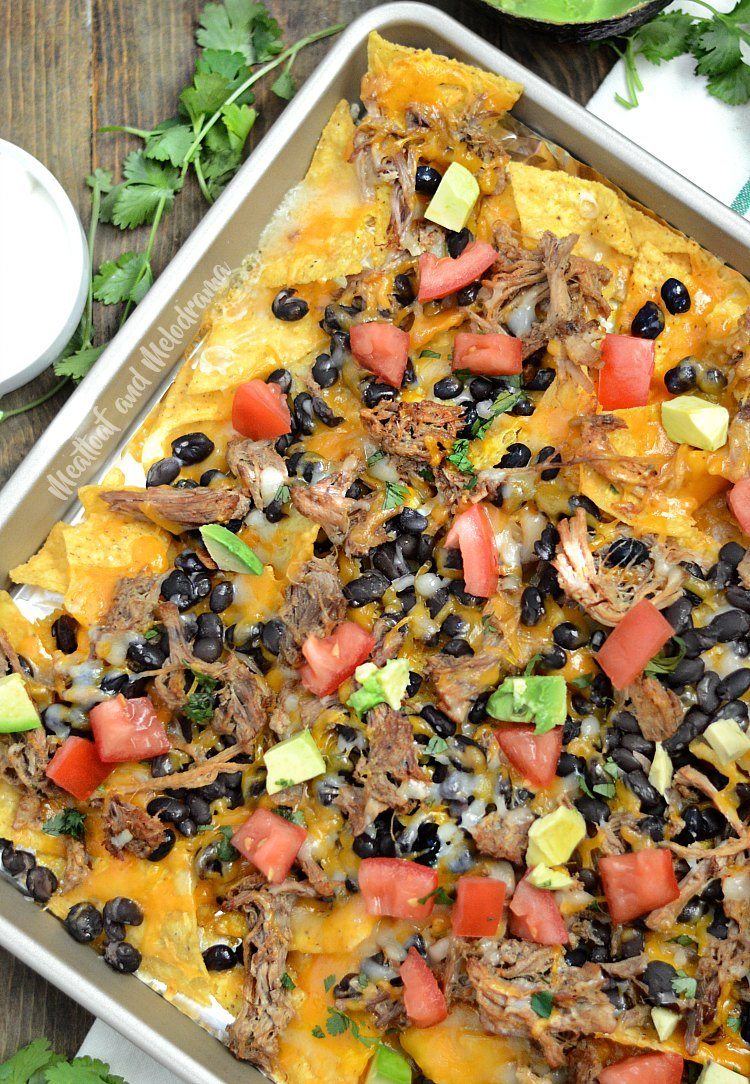 sheet pan pulled pork nachos with black beans and tomatoes and avocado