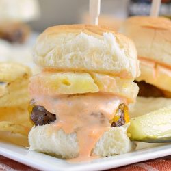 spicy habanero beef sliders with pineapple and cheddar cheese on white plate with pickle and chips