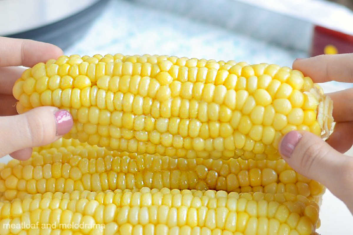 instant pot corn on the cob with butter in hands