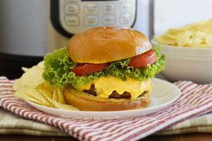 instant pot hamburger with melted cheese, lettuce and tomato slices on a bun with chips