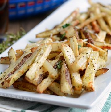 homemade baked french fries with rosemary on white platter