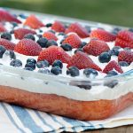 red white and blue poke cake on picnic table