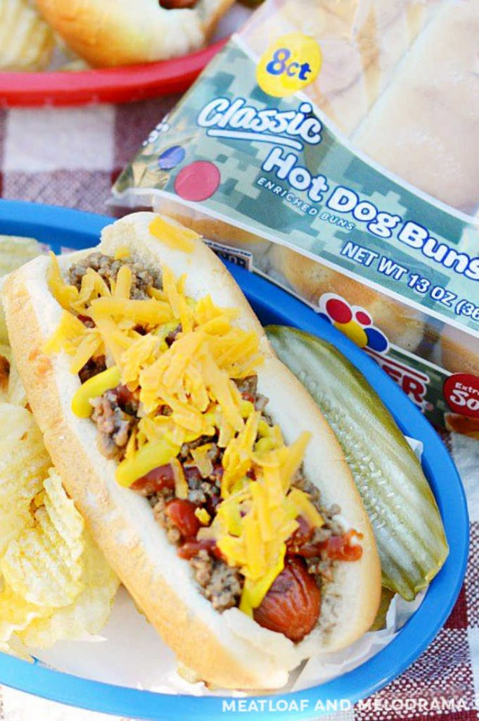 overhead view of hot dog in bun topped with cheese and beef