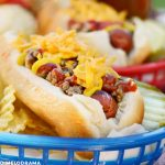 cheeseburger hot dog in blue basket with chips