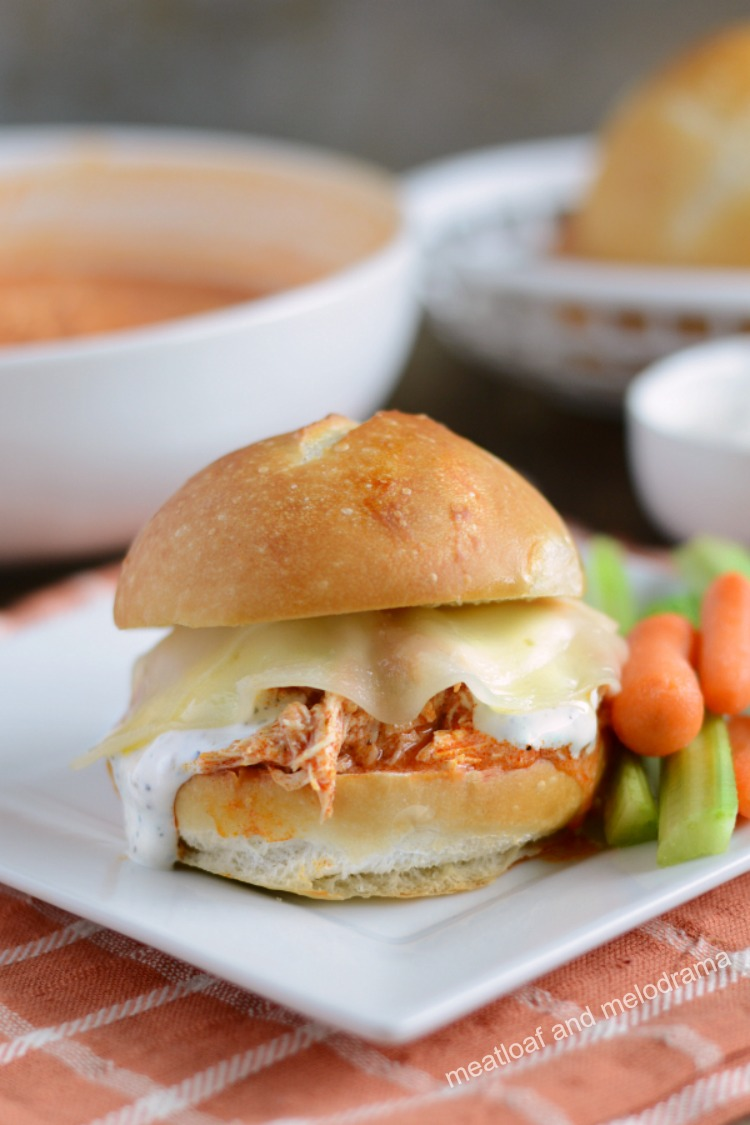 instant pot buffalo chicken sliders with ranch and provolone on plate with carrots and celery
