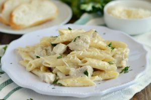 instant pot chicken alfredo penne pasta on white plate with parsley