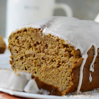 easy pumpkin bread recipe with powdered sugar cinnamon spice glaze on a plate
