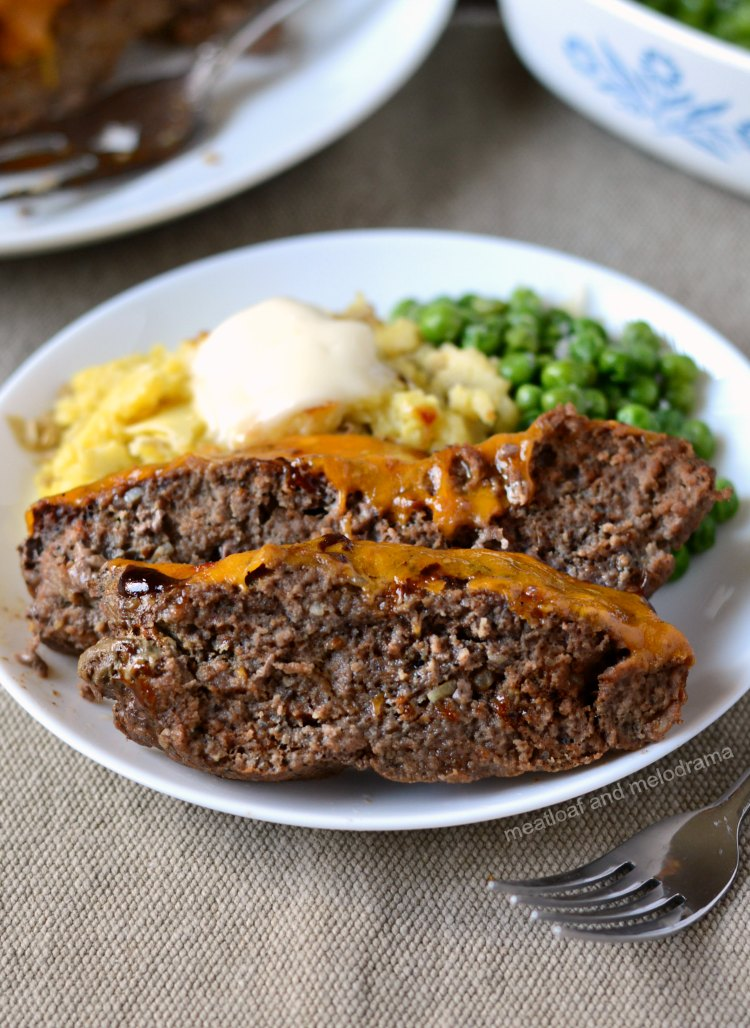 instant pot meatloaf with cheddar bbq sauce on plate with mashed potatoes and peas