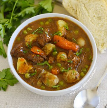 instant pot beef stew with red wine potatoes and carrots and peas in white bowl