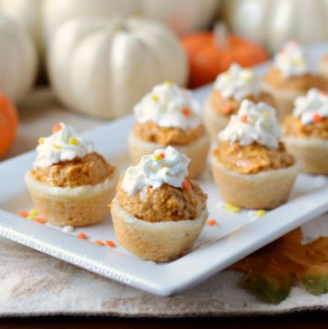 pumpkin cheesecake cookie cups with whipped cream on a serving tray for Thanksgiving