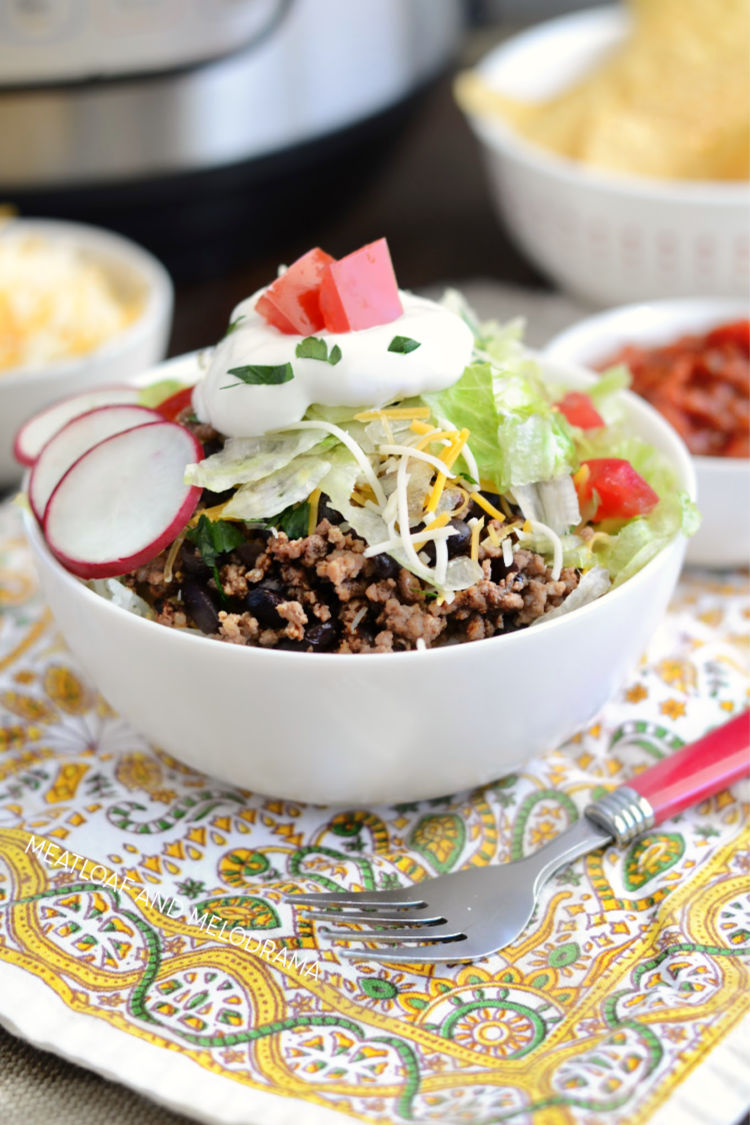 instant pot beef taco meat with black beans and rice in taco bowl