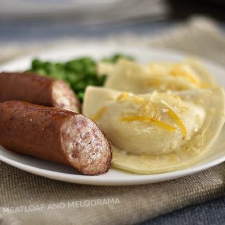 baked pierogies and kielbasa sausage on white plate with peas