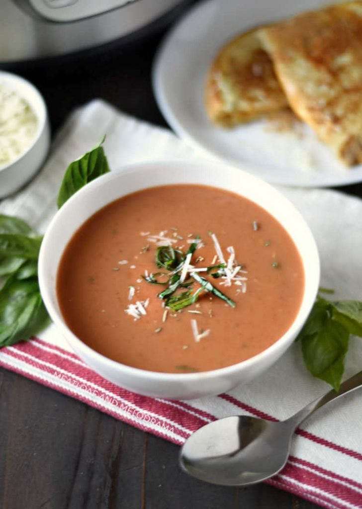 instant pot creamy tomato basil soup in white bowl with basil leaves and parmesan cheese