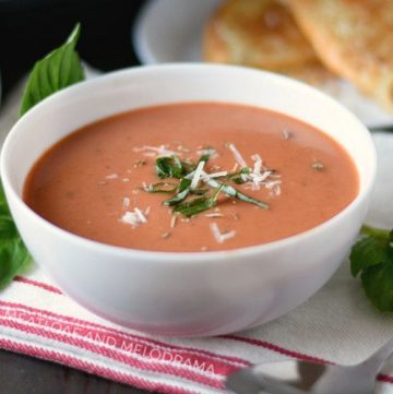 instant pot creamy tomato basil soup with parmesan and basil in a white bowl