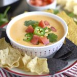 instant pot queso dip in a bowl with tortilla chips and tomatoes and jalapeno peppers