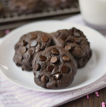 double chocolate chip cookies on a white plate with a glass of milk