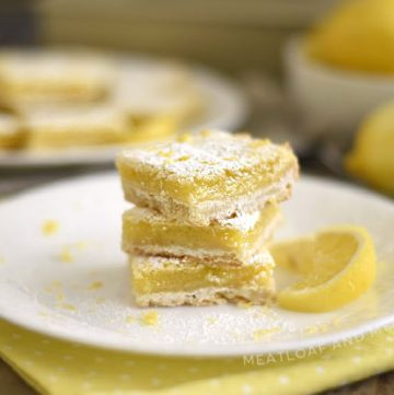 easy lemon bars with shortbread crust and powdered sugar topping on white plate