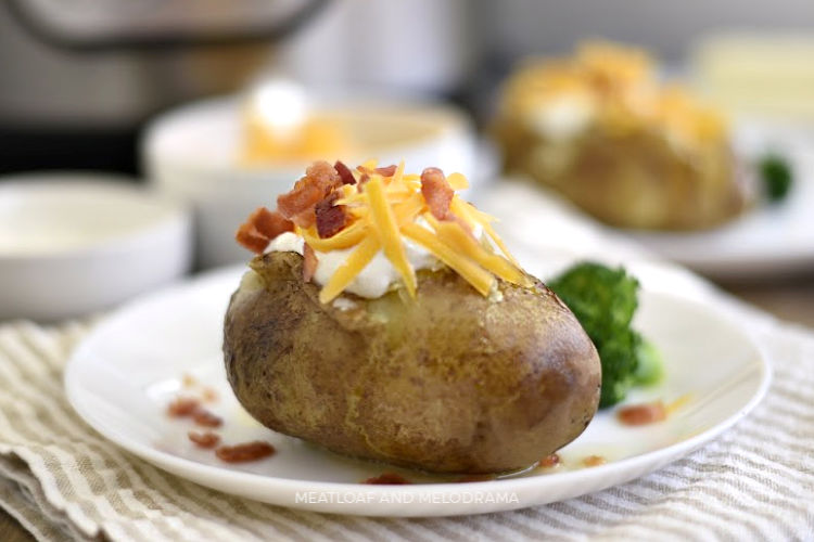 instant pot baked potatoes with sour cream cheddar cheese and bacon on a plate