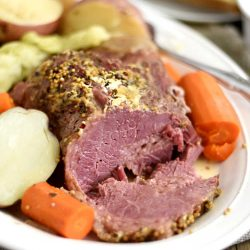 instant pot corned beef and cabbage with carrots and red potatoes on white platter