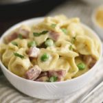 instant pot ham and cheese tortellini with peas in a white bowl