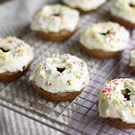 baked carrot cake donuts with cream cheese frosting on baking rack