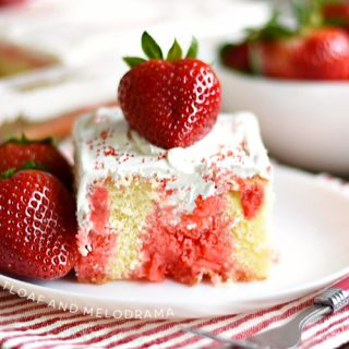 strawberry jello poke cake with strawberries on a white plate