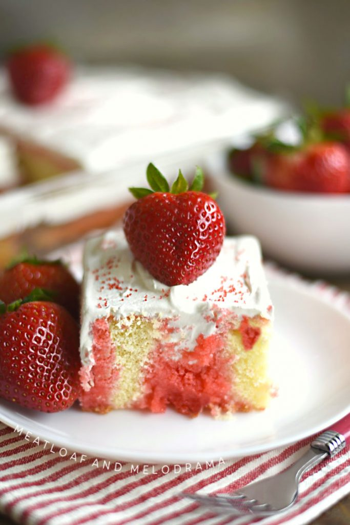 strawberry jello poke cake with whipped topping and fresh strawberries on white plate