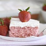strawberry cream soda cake with whipped topping and strawberry on white plate
