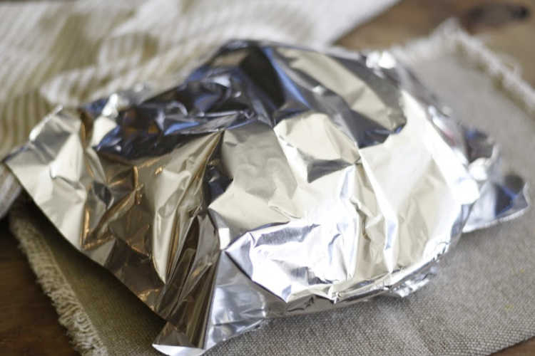 easy microwave baked potatoes on a plate covered with foil