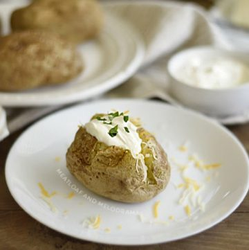 microwave baked potatoes on a plate with sour cream and butter