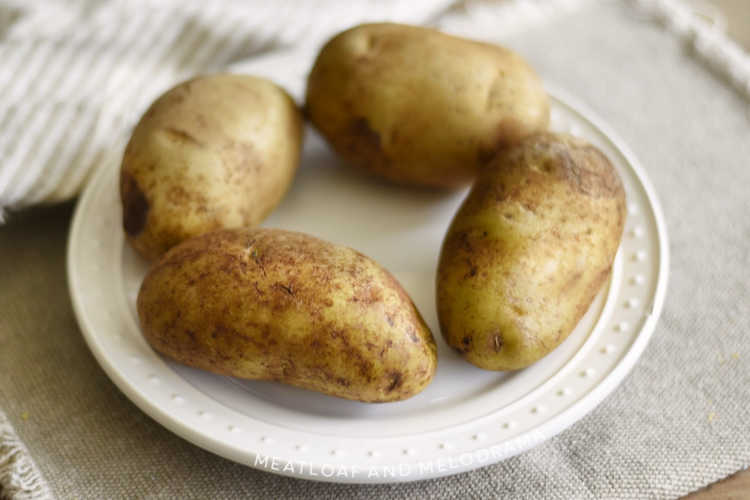 scrubbed russet potatoes on white plate